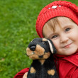 Little girl with a toy dog in park — Stock Photo