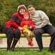 Married couple and little girl sit on a bench in park in autumn - Stock Photo