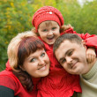 Married couple and little girl in park in autumn - Stock Photo