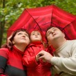 Married couple and  little girl with umbrella in park - Stock Photo