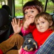 Woman and  little girl  Greeting to wave hands in car in park — Foto de Stock