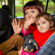 Woman and  little girl  Greeting to wave hands in car in park — Lizenzfreies Foto