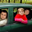Married couple and  little girl sit in car in park - Stock Photo