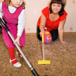 Little Girl and woman vacuum a carpet — ストック写真