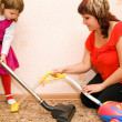 Stock Photo: Little Girl and womvacuum carpet