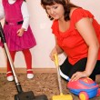 Little Girl and woman vacuum a carpet — Photo