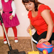 Stock Photo: Little Girl and woman vacuum a carpet