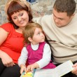 Married couple and  little girl read  book in a cosy room - Stock Photo