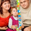Stock Photo: Married couple and little girl playing cubes in cosy room