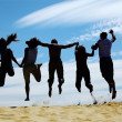 Group of friends jumps on sand, rear view - Stock Photo
