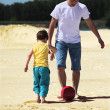 Father with son play football on sand — Stockfoto