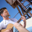 Guy plays guitar and lip accordion sitting on sand — Stock Photo #7427253