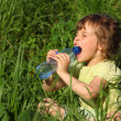 Girl sits in grass and drinks water from plastic bottle - Stock Photo
