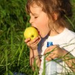 Girl with plastic bottle eats green apple in grass — Stock Photo