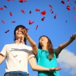 Young pair scatters petals of roses against sky — Stock Photo #7427515