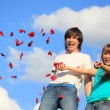 Young pair scatters petals of roses against sky — Stock Photo