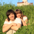 Girl embraces guy behind for shoulders among grass — Stock Photo