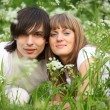 Young pair sits in grass — Stock Photo