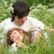 Girl lies in lap of guy sitting in grass — Stock Photo #7427620