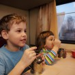 Two children drink tea from glasses in train car — Stock Photo