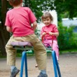 The boy and the girl on a swing in park — Stok fotoğraf