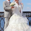 The newly married couple near river, focus on bouquet — Stock Photo