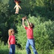 Stock Photo: Boy and girl in park toss up upward doll