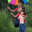 Boy and girl under umbrella in park tear grass — Stock Photo