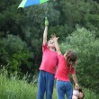 In park boy holds umbrella over head,  girl pulls to it hand — Stock Photo