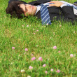 Businessman lies on back on grass with closed eyes — Stock Photo #7427892