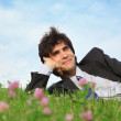 Businessman lies on grass on one side with closed eyes — Stock Photo #7427896