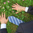 Businessman lies prone on grass, top view — Stock Photo
