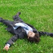 Businessman lies on back on grass, having stretched legs and han — Stock Photo