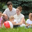Stock Photo: Family of five outdoor in summer sit on grass with ball