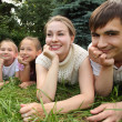 Family of four lying on grass and looks — Stock Photo #7427999