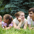 Family of four lying on grass and looks on each other — Stock Photo #7428002