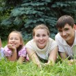 Stock Photo: Family of four lying on grass and looks