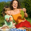 Pretty Little Girl and Young Women keeps in hand fruits on picni — Stock Photo #7428015