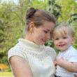 Mother hold baby on hands outdoor in summer — Stock Photo