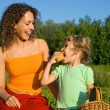 Pretty Little Girl and Young Women eats fruits on picnic — Stock Photo