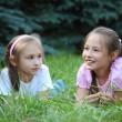 Two girls lie on grass in summer — Stock Photo