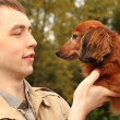 Young man and his adorable dachshund closeup - Stock Photo