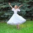 Stock Photo: Girl in white dress dances on lawn with lifted hands