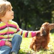 Little girl with dachshund sits on grass — Stock Photo