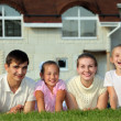 Family from four lies on grass against house - Stock Photo