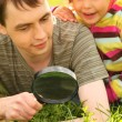 Young man and little girl look through magnifier — Stock Photo
