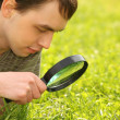 Young man looks through magnifier — Stock Photo