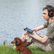 Young man liistens music in headphones sits on grass with his da — Stock Photo