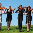 Four musicians go and playing violins against sky, front view — Stock Photo