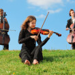 Violinist and two violoncellists play on grass against sky - Zdjęcie stockowe